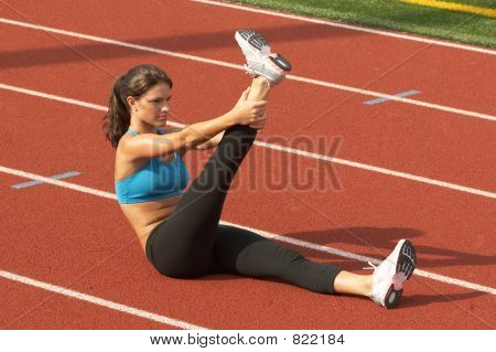 Young Woman in Sports Bra Stretching Raised Leg on Running Track