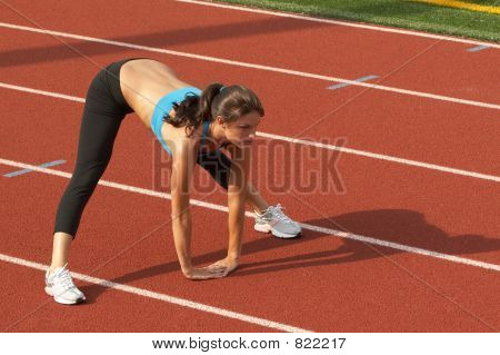 Young Woman in Sports Bra Leaning Forward and Stretching Hamstrings