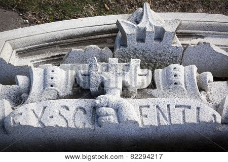 ANNAPOLIS, MARYLAND- DECEMBER 27, 2014: A hand made of granite holding a trident in front of the Latin words Ex Scientia salvaged from a US Naval Academy building facade.