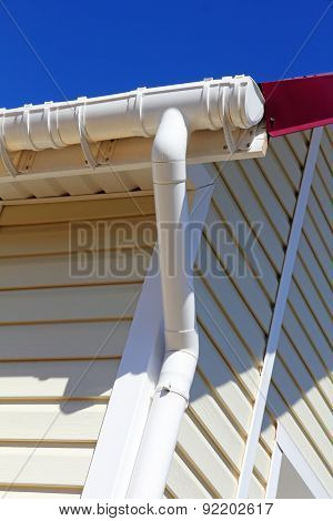 New Plastic Rain Gutter System With Drainpipe  On White Wall.
