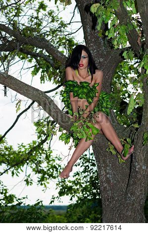 beautiful woman in leaves sitting on a tree