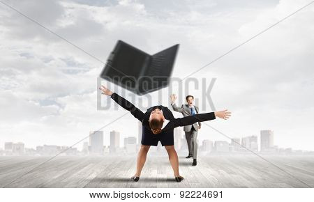 Young businesswoman trying to evade from thrown laptop