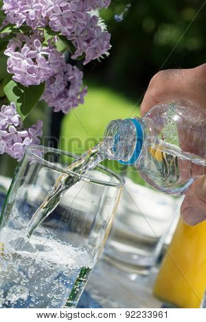 Man's Hand Pouring Water From A Bottle Into A Glass On A Garden Table