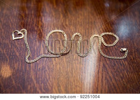 gold chain arranged in form of word Love