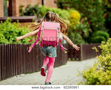 little girl with a backpack run  to school. back view