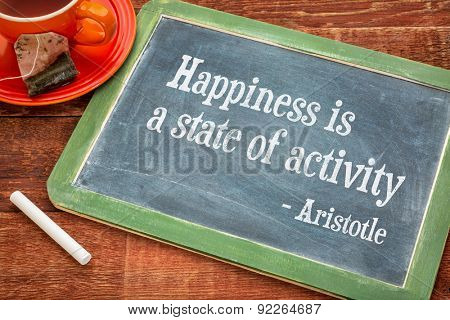 Happiness is a state of activity, a quote from Aristotle - motivational words on a slate blackboard with chalk and cup of tea
