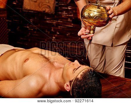 Young  handome man having Ayurveda spa treatment with pouring oil on head.