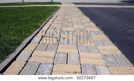 A walkway made of brick pavers, with a lawn on one side, and a blacktop driveway on the other. poster