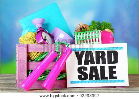 Crate of unwanted stuff ready for yard sale on bright background poster