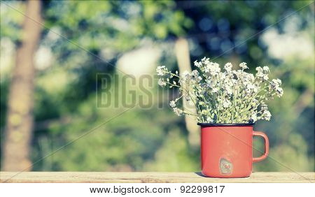 Summer background with forget me not flowers in a jar on wooden background