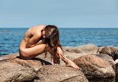 BW image of beautiful young sexy nude woman siting on stones by the sea. poster
