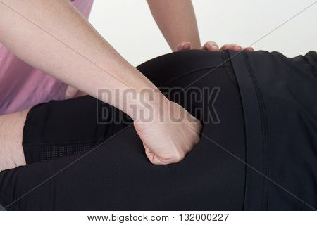 Physiotherapist Massaging Buttocks Of Patients In Medical Office