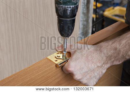 Door installation Install hinges for wooden interior door carpenter screwing screws close-up.