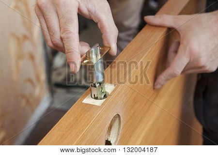 Installation locked interior door knobs close-up woodworker hands install lock.