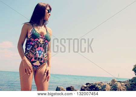 Beautiful young woman posing next to the sea