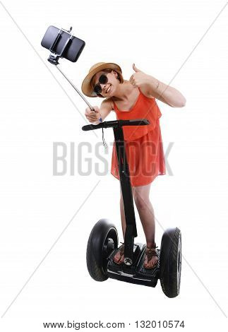 young chic tourist woman taking selfie photo with mobile phone while riding on segway urban transport having fun isolated on white background in vacation tourism concept