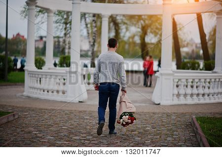 Marriage Proposal. Man With Boquet Of Flowers Goes To Meet His Girlfriend