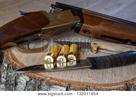 hunting rifle and ammunition, cartridges, on a wooden table.