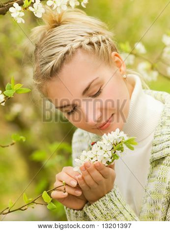 Beautiful young woman looking at ladybug on flowers