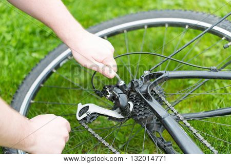Man adjusts the derailleur bike. black moutain bike poster