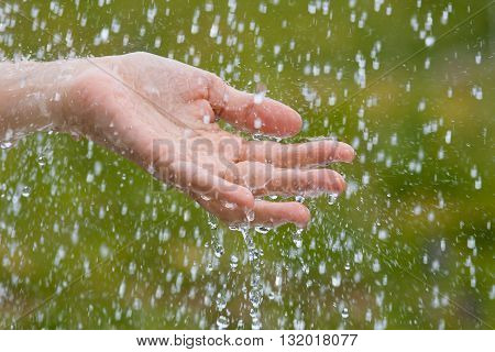 hand of woman catching raindrops on blurred background
