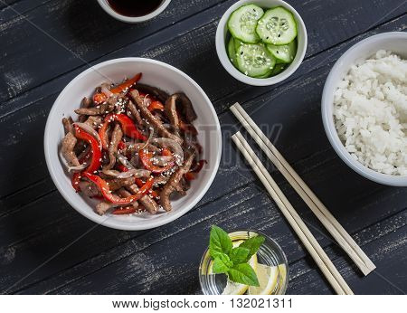 Meat stir fry with sweet red pepper steamed rice and fresh cucumber and sesame salad on dark wooden background