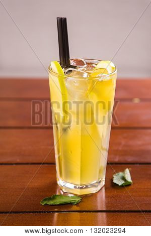 cold fresh apple tea with ice and straw in studio