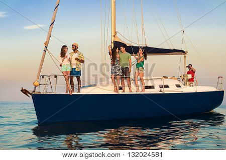 Young people standing on yacht. Guys and girls smiling. Captain at the helm. Time well spent.