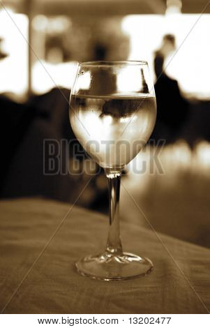 Glass of white wine on a table (toned in sepia)