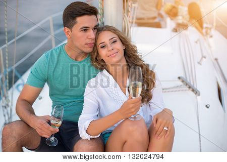 Man with woman on yacht. Smiling people hold wineglasses. Pure magic of love. Lovers amidst the ocean.