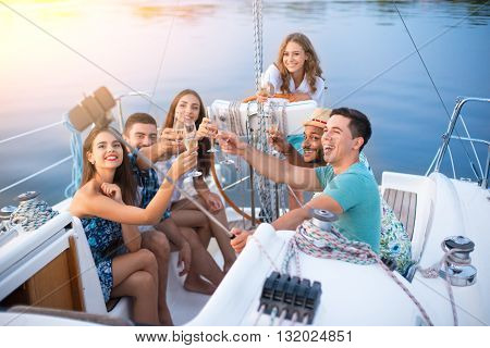 People with drinks taking selfies. Guys take selfies on yacht. Weekend party at sea. Friendly atmosphere and honest smiles.