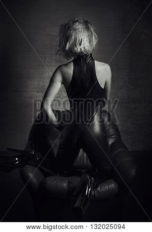 Sexy woman dominatrix in latex catsuit kneeling on sofa in dark black and white