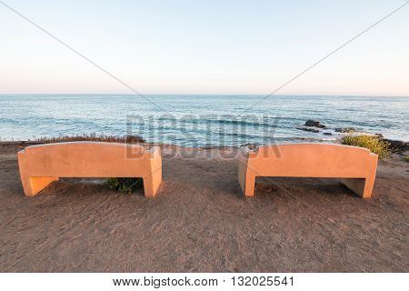 Two public benches overlooking the Pacific ocean at Carpinteria State Park California.