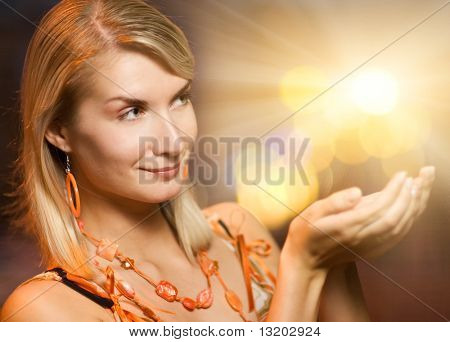Beautiful woman holding magic lights in her hands