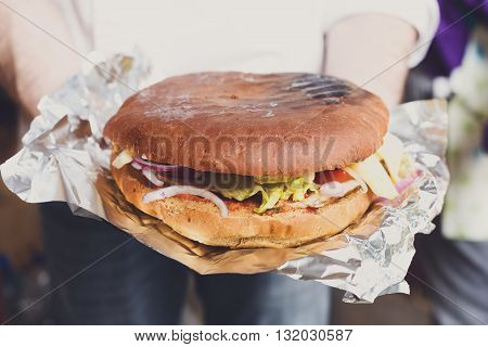 Fresh hamburger cooked at barbecue outdoors. Cookout american bbq food. Big burger with pork steak meat, sauce and vegetables closeup in chef's hand on foil. Street food, fast food.