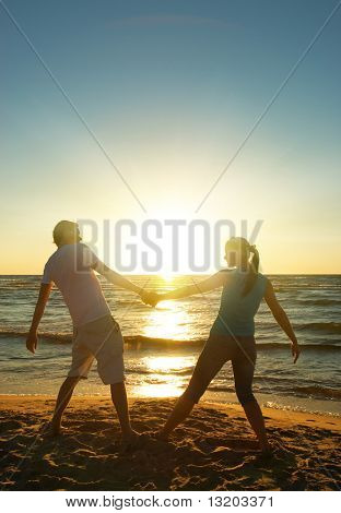 Man and woman relaxing near the ocean at sunset