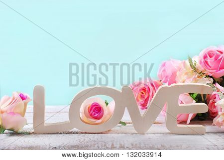 romantic love background in pastel colors with standing wooden word love and roses