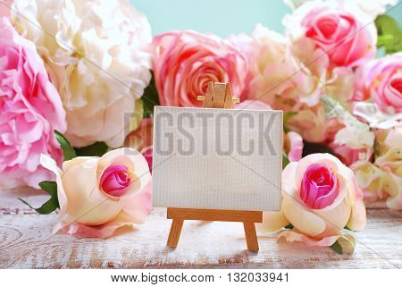 small easel standing among roses with empty board for own text