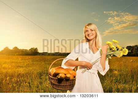 Beautiful young woman with a basket full of fresh baked bread