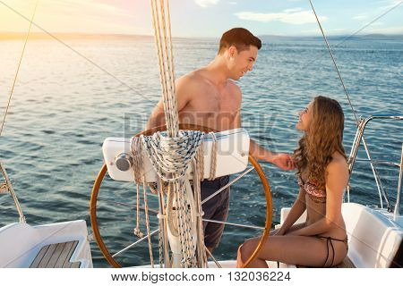 Smiling man beside yacht wheel. Girl and guy on boat. Let me tell you something. Don't be shy.