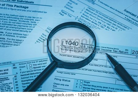 Personal tax form us with magnifying glass and pen in business blue macro
