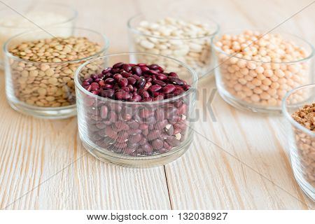 Grain and beans in glass bowls on a white wooden background. Various types of grain. beans, peas, buckwheat, lentils, rice. background of white boards. healthy food concept.