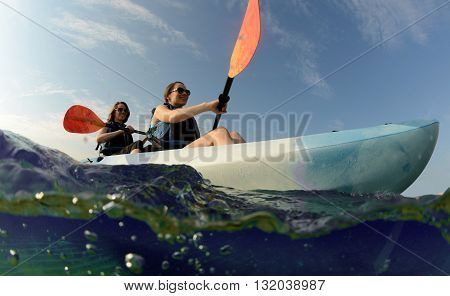Two young women smiling in blue kayak in tropical ocean