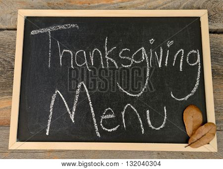 Thanksgiving menu written in chalk on a chalkboard on a rustic background