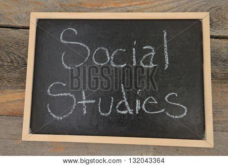 social studies written in chalk on a chalkboard on a rustic background