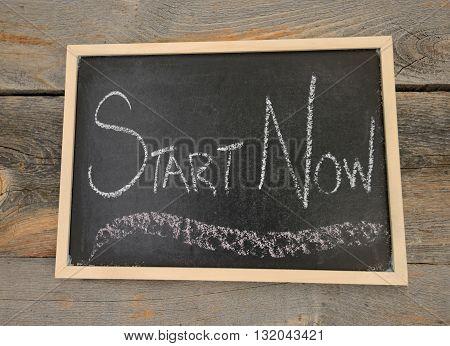Start Now written in chalk on a chalkboard on a rustic background