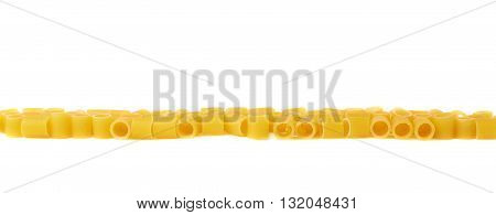Line made of dry ditalini yellow pasta over isolated white background