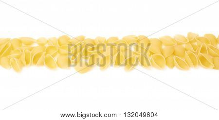 Line made of dry conchiglie yellow pasta over isolated white background