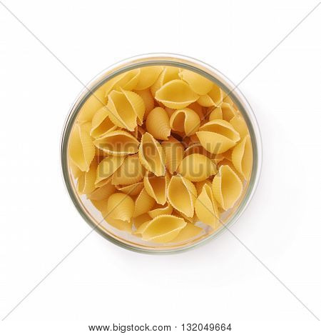 Glass jar filled with dry conchiglie yellow pasta over isolated white background