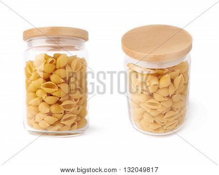 Set of glass jar filled with dry conchiglie yellow pasta over isolated white background, different foreshortenings